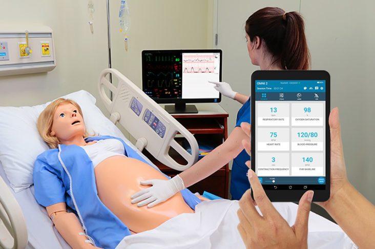 Dispositivo OMNI 2 em primeiro plano e simulador Noelle em leito hospitalar ao fundo