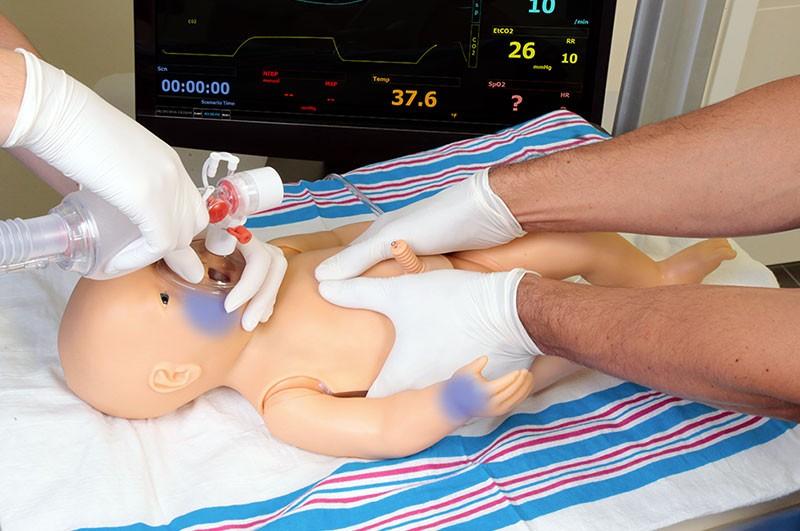 Simulador de recém-nascido recebendo cuidados de RCP e BVM