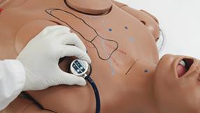 Profissional colocando auscultador do estetoscópio no peito do simulador