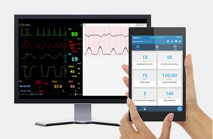 Dispositivo Omni 2 em primeiro plano e monitor com sinais vitais ao fundo