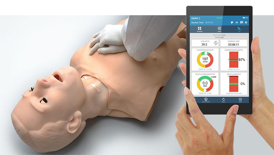Dispositivo OMNI 2 com interface do software e profissional realizando RCP no simulador S315.100.250 ao fundo