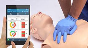 Dispositivo OMNI 2 com interface do software e profissional realizando RCP ao fundo