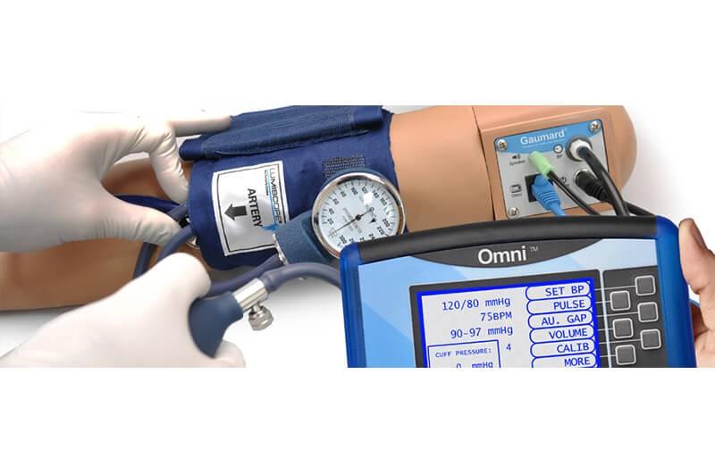 Profissional aferindo pressão no braço do simulador